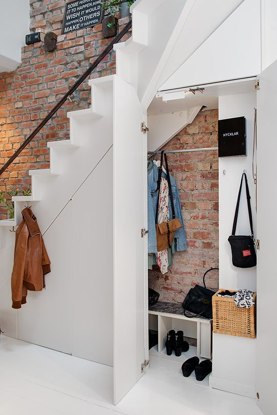 entryway cabinet and bench under the stairs features a brick wall that continues above