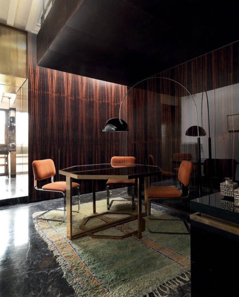 The dining area is very cozy, dark and moody, rosewood and orange chairs look amazing together