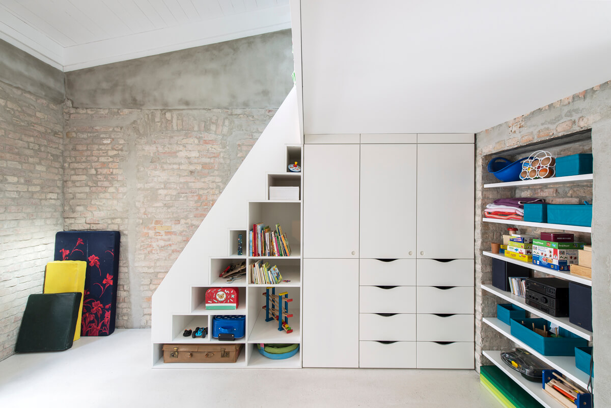 The kid's playspace has a lot of storage cabinets and shelves and a private bedrom area above the stairs