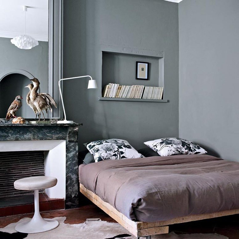 The master bedroom is done in graphite grey, there's another cool fireplace and a rough wood bed in the corner
