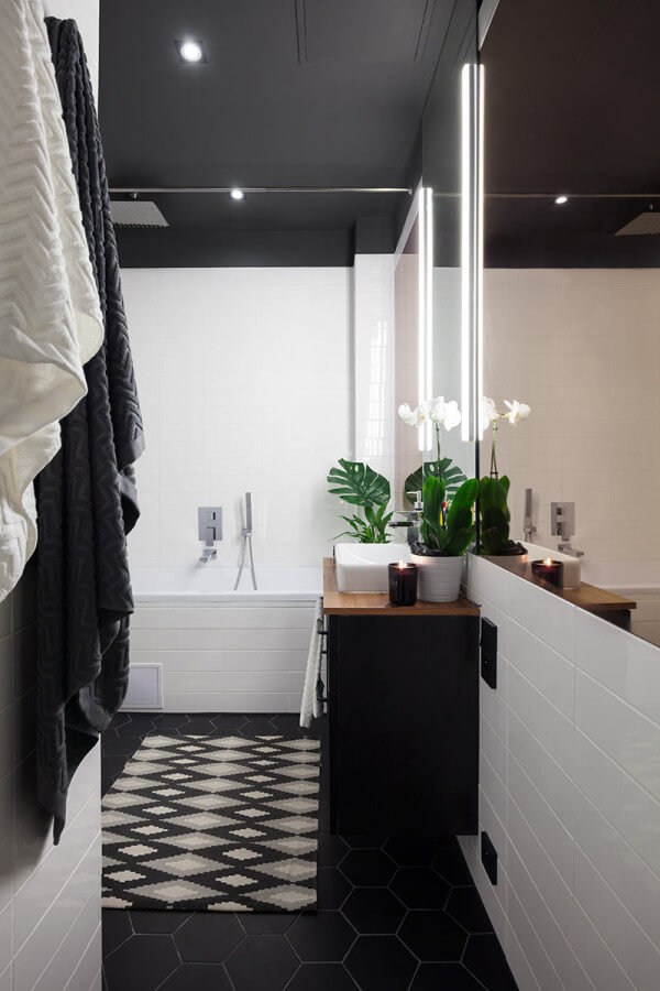 The simple and timeless black and white bathroom is accentuated with potted orchids