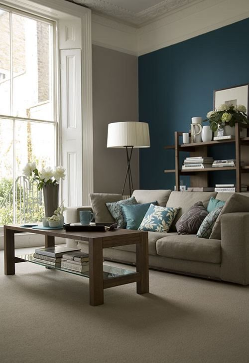 Grey and beige room with a teal accent wall blue pillows and