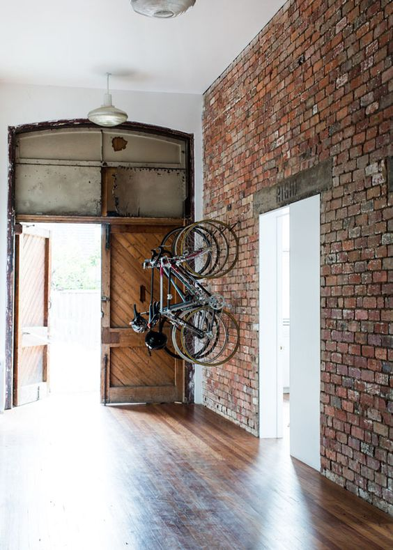 large entryway with an exposed brick wall that features bike holders
