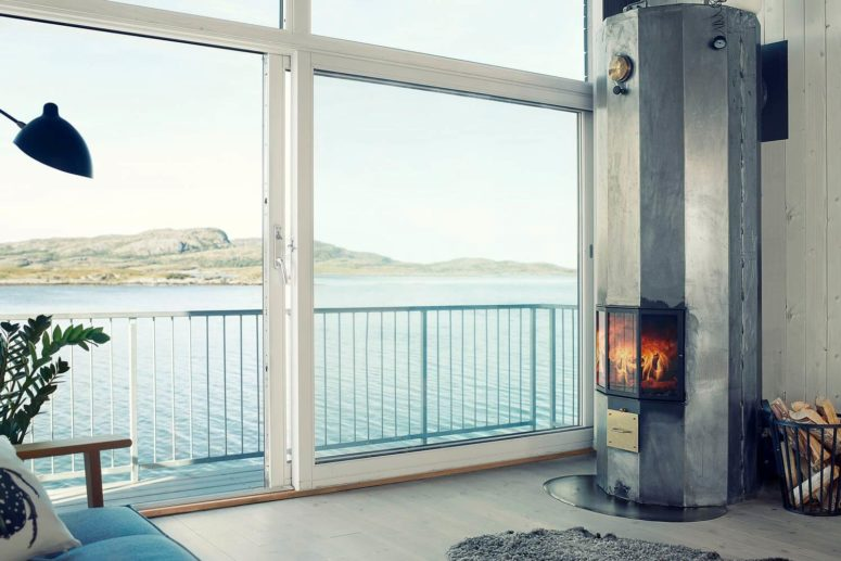 A hearth brings coziness in, and with a waterfront views next to it, it looks amazing