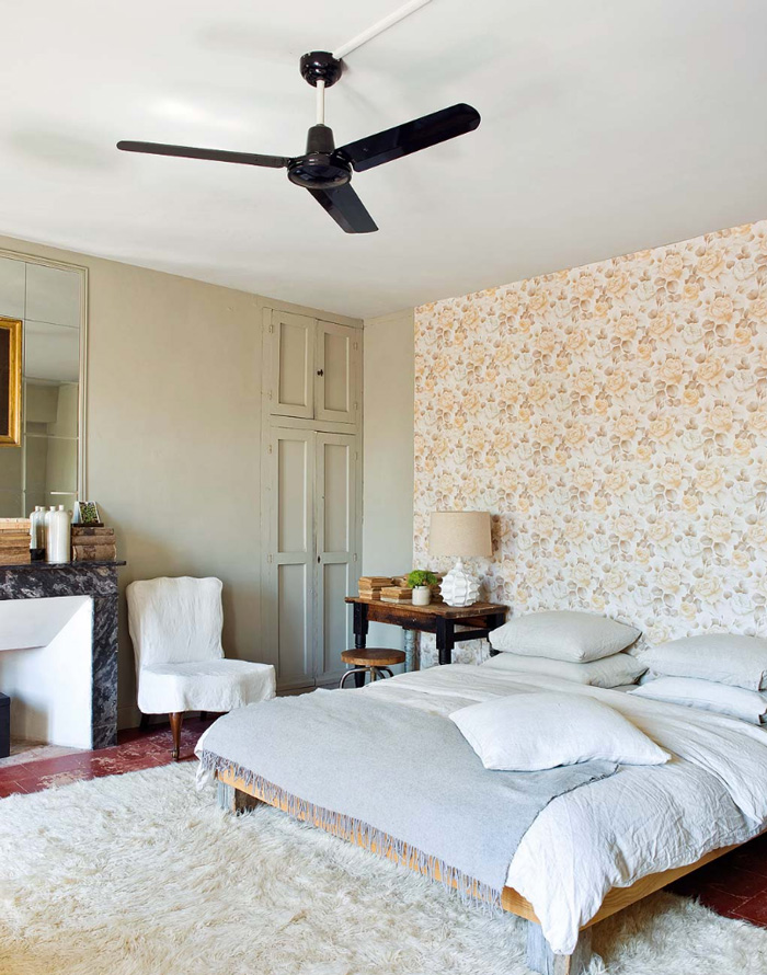 Another bedroom is pastel and full of light with pretty printed wallpaper and a fluffy carpet