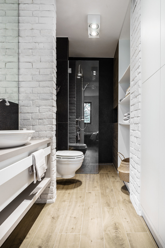 The bathroom is covered with whitewashed brick panels and features sleek surfaces