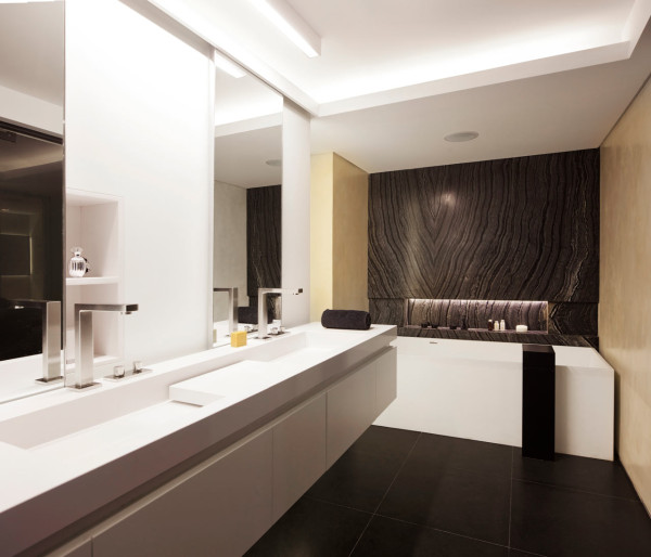 The master bathroom is done in white but there's a gorgeous black marble panel installed behind the bathtub