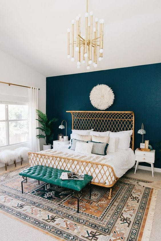 masculine meets feminine bedroom with a teal headboard wall and gilded accessories