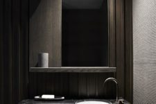 08 modern bathroom space with dark wood panels, a black marble counter and a large mirror