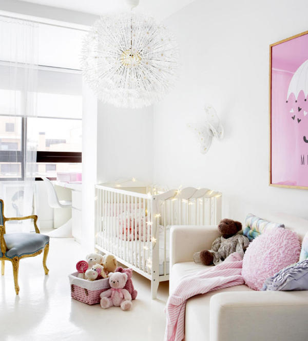 The kid's room is done in white and pink, with a cute lamp and a couple of refined touches