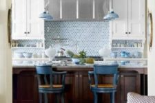 09 blue penny tile and delft pottery lend a watery inluence to this kitchen with white cabinets and stainless steel hood