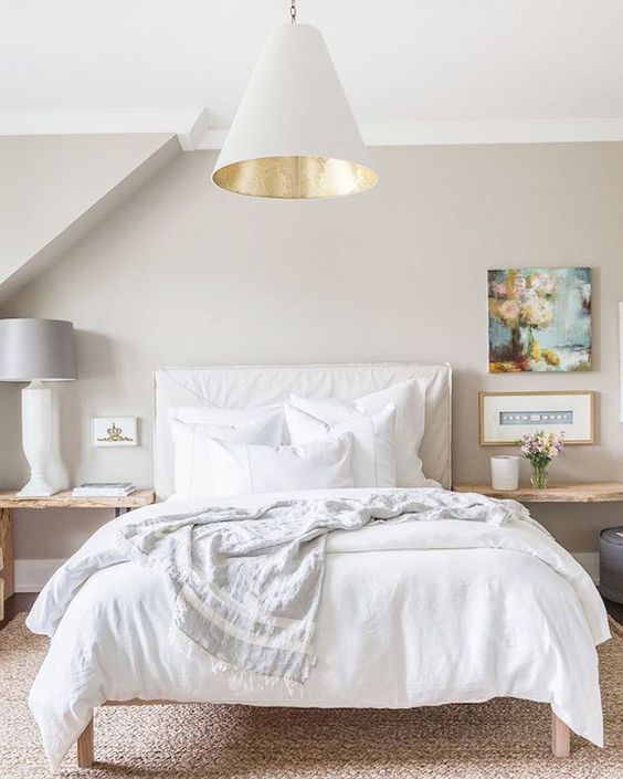 cozy bed with neutral bedding and pillows looks welcoming