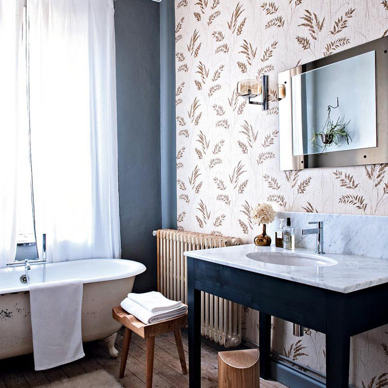 The master bathroom has a rural print wallpaper wall, a modern mirror and faucet and lots of rustic touches