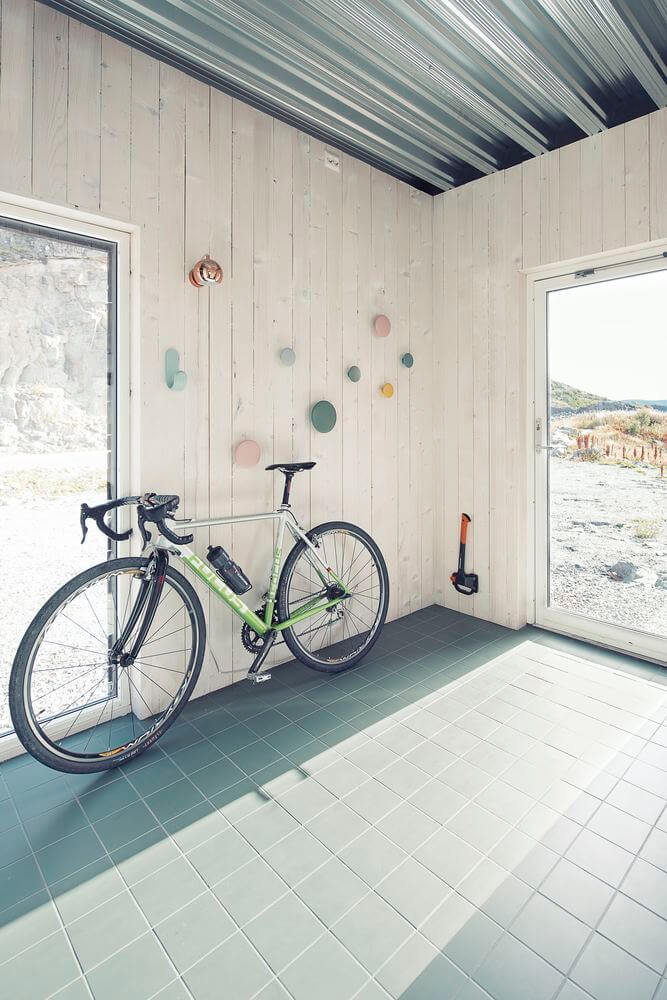 The entryway has a lot of light in due to a glass door and it features a bike stand