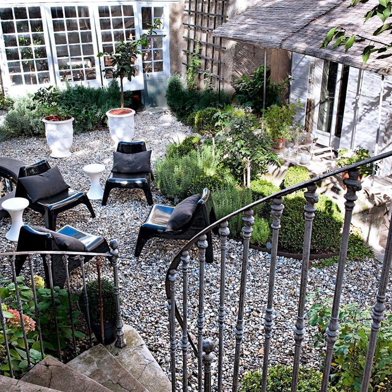 The small garden looks like a heaven with herbs and lavender in antique pots and modern black chairs