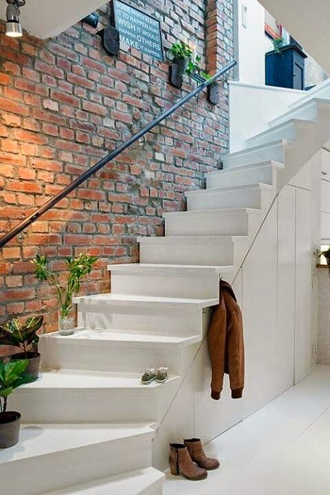 exposed brick wall above the stairs gives a style to this entryway