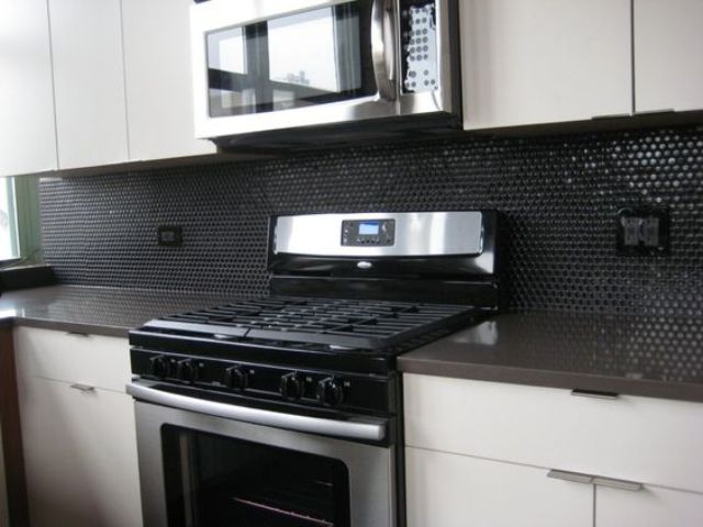 glossy black penny tiles for a minimalist black and white kitchen
