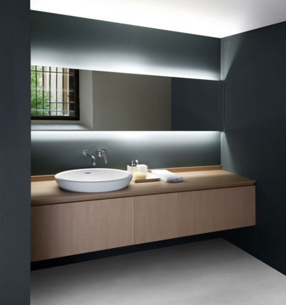 minimal countertop washbasin and gorgeous hidden lighting behind the mirror