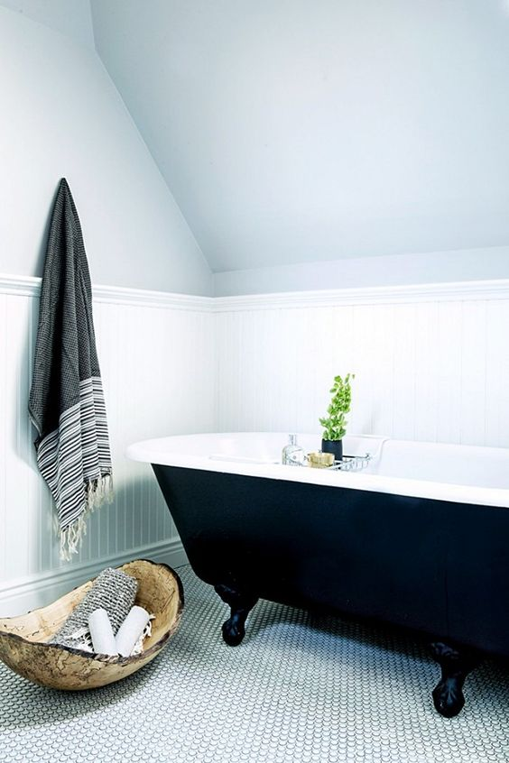 simple bathroom with penny tile floors and a black clawfoot tub