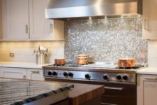 12 glowing silver penny tile backsplash looks great with a stainless steel hood