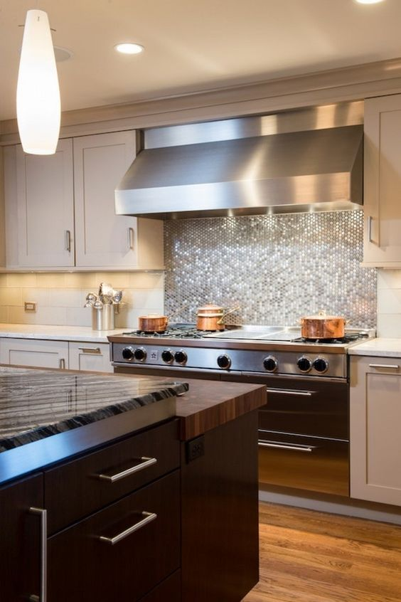glowing silver penny tile backsplash looks great with a stainless steel hood