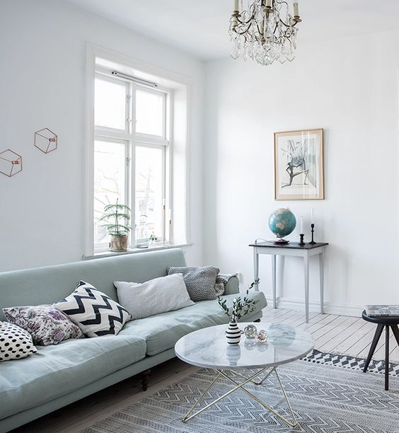 light-filled room with a mint green sofa
