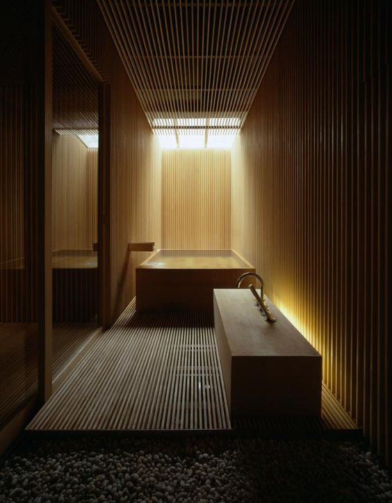bathroom totally clad with light wood with hidden lights look relaxing and a bit mysterious