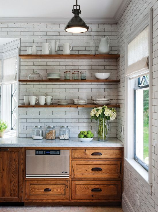 rustic kitchen with wooden cabinets and walls covered with subway tiles