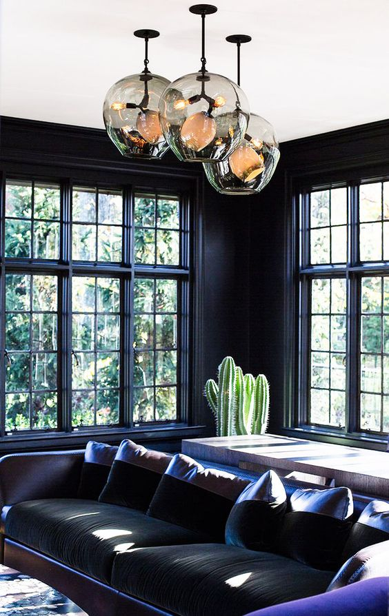 dark hued room with purple accents, cact and unique pendants
