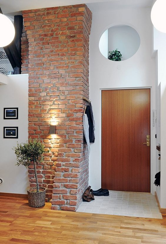 large brick pillar gives a stylish look to both the entryway and the kitchen next to it