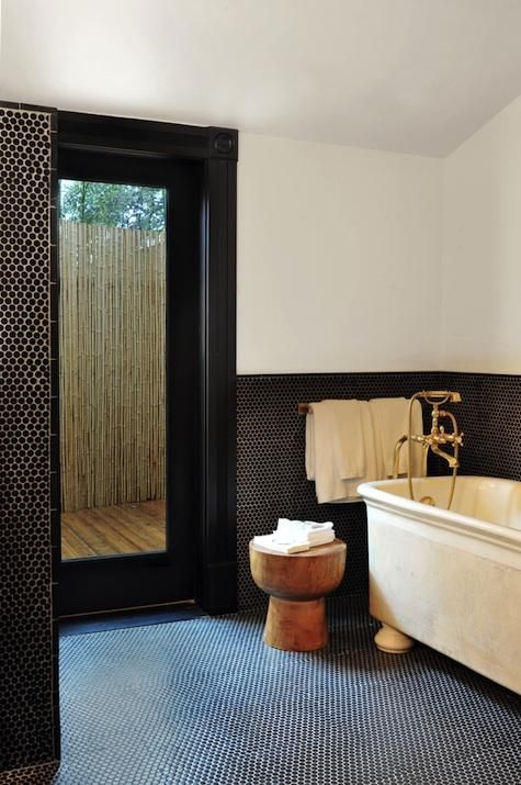 Black Penny Tiles On The Floor And Walls Create Stylish Decor