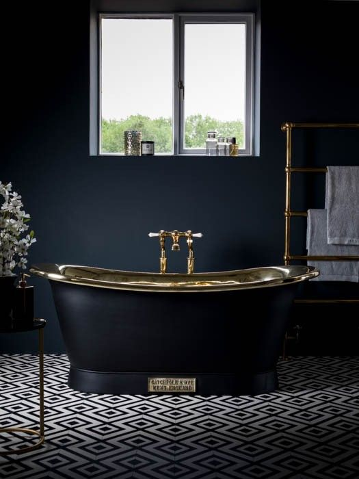 charcoal grey bathroom with brass accents and a retro free-standing bathtub