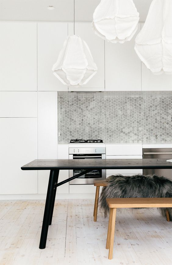 minimalist white kitchen is spruced up with grey tiles of various tones