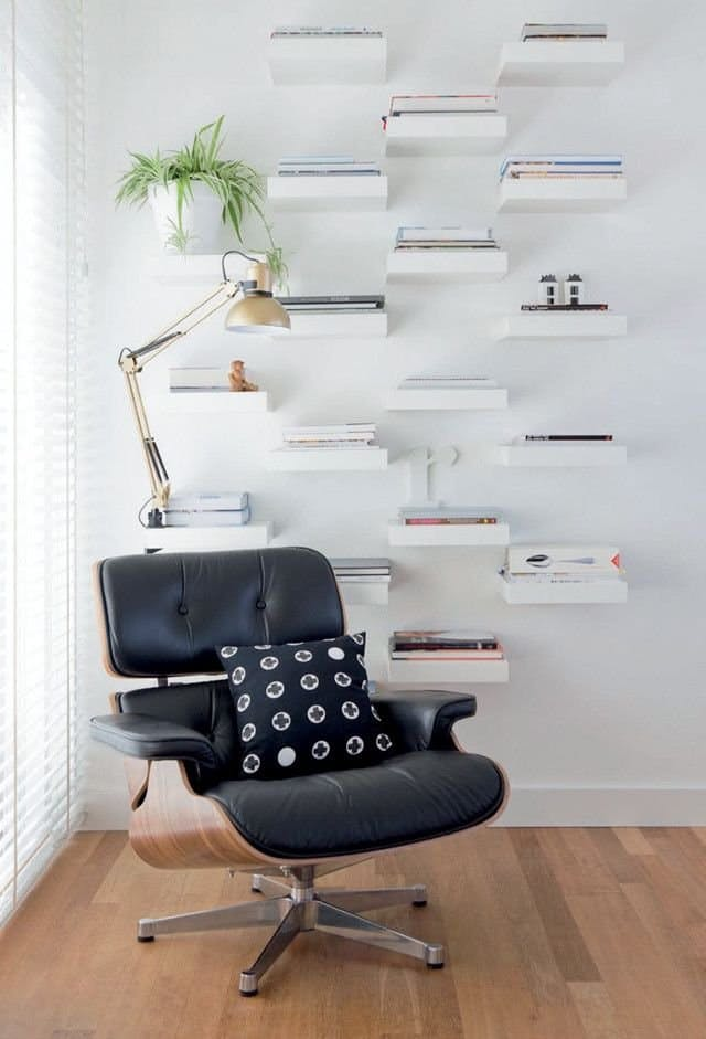 a wall of little shelves that creates a library in the living room