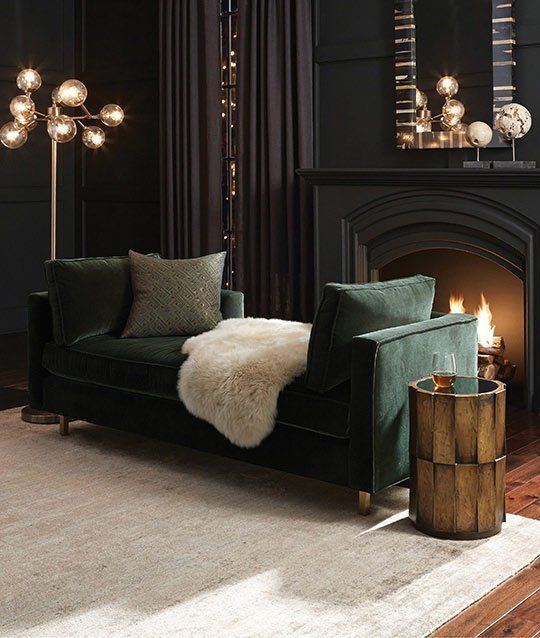 soft black living room with a dark green sofa art deco lights and a