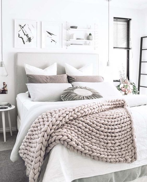 a chunky knit wool throw adds texture and interest to this neutral bedroom