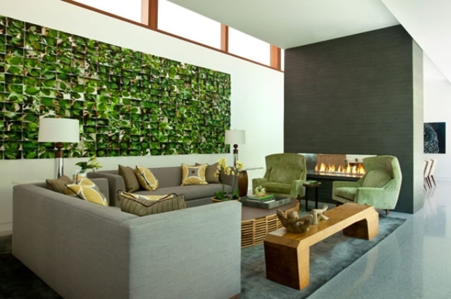 grey living room is spruced up with green chair and a striking wall mural