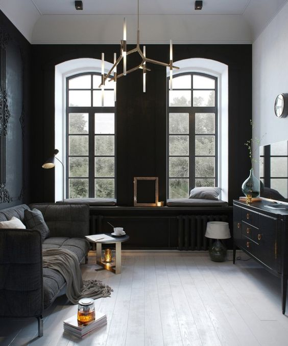 small dark sitting room, chic modern furniture and a unique brass chandelier