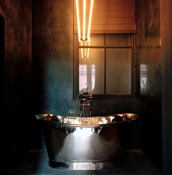 industrial space with a metallic bathtub for a masculine bathroom