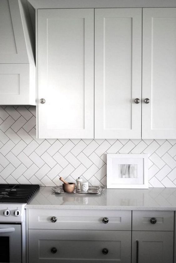 kitchen backsplash clad in subway tiles with a diagonal herringbone pattern