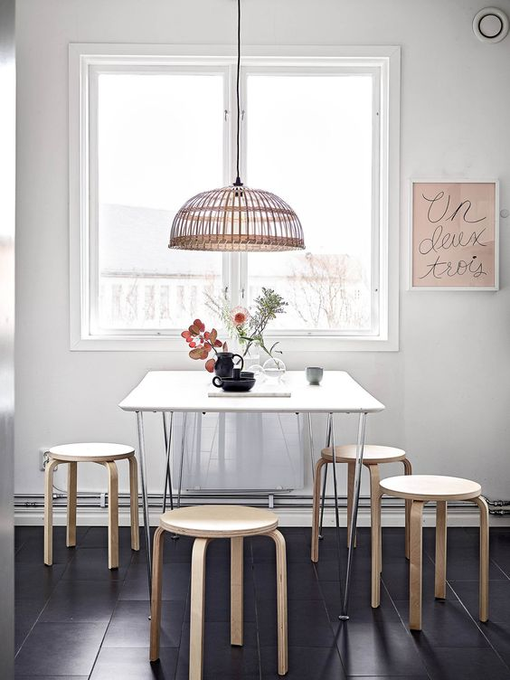 simple dining room with Ikea Frosta stools and a basket lamp