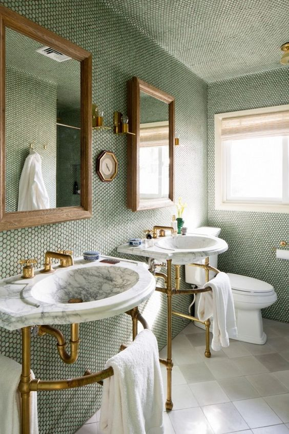 bathroom with brass and marble fixtures and a wall of moss-green penny tiles