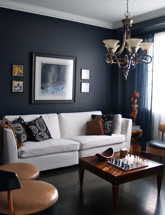 masculine space with a dark navy accent wall, tan chairs, warm wood furniture and accessories