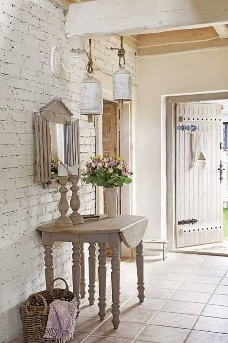 shabby chic entryway with a whitewashed brick wall and wooden table and candle holders