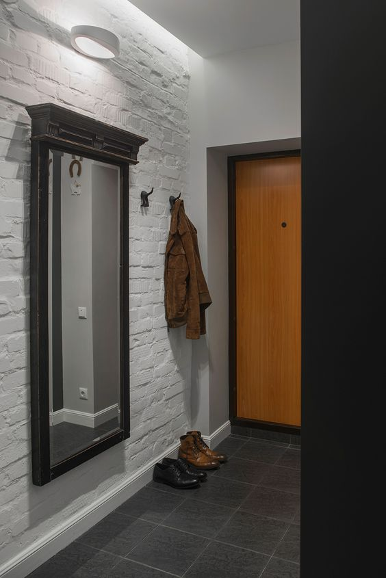 laconic bachelor entryway with a white brick wall