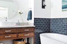 21 the bathing space in this rustic bathroom is highlighted with navy subway tiles