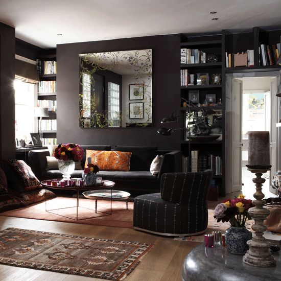 dark living room with black walls, colorful accessories and various textiles