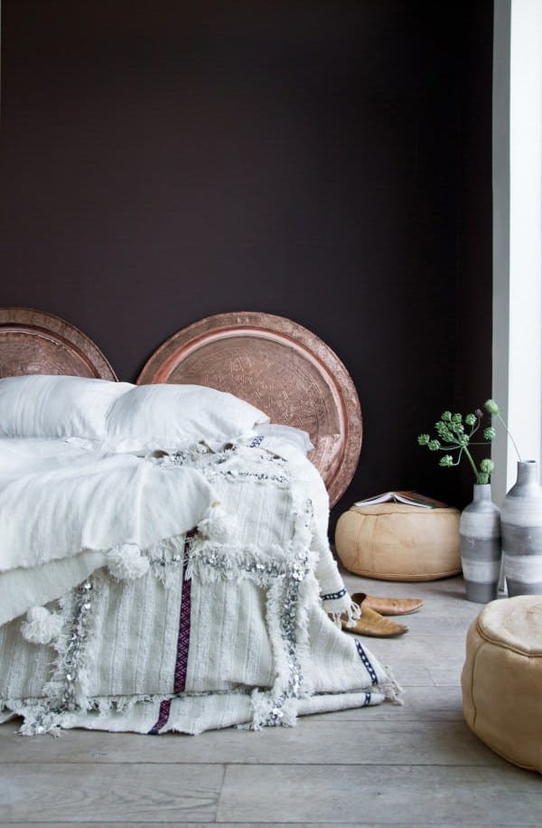 soft bedding and copper dishes instead of headboards in an Eastern room