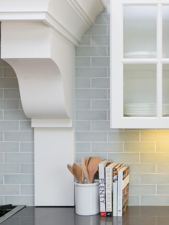 subway tiles in a pale blue-gray give depth to the backsplash and make the white cabinetry feel even more fresh