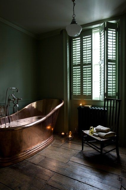 vintage bathroom with a copper bathtub and green walls